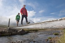 Low angle view of mature hiking couple crossing wooden footbridge, Breidvik, Borgafjordur East, East Iceland — Stock Photo