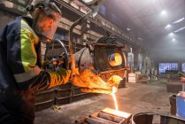 Worker pouring molten metal into moulds in foundry — Stock Photo