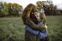 Mother and daughter hugging in meadow, Lakefield, Ontario, Canada — Stock Photo