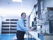 Ingénieur de compatibilité électromagnétique effectuant un balayage des émissions rayonnées sur les équipements électriques dans une chambre anéchoïque en utilisant une alimentation haute performance et un analyseur de réseau — Photo de stock