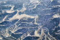 Aerial view of snowcapped mountain range in sunlight — Stock Photo