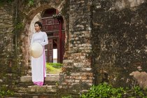 Mid adult woman wearing ao dai dress standing on step holding conical hat looking away, Hue, Vietnam — Stock Photo