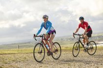 Cyclists riding on gravel road on sunny day — Stock Photo