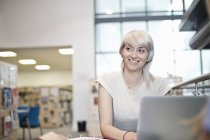 Young woman using laptop in library — Stock Photo