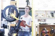 Жінка в майстерню з ремонту велосипедів проведення буфер обміну, перевірка велосипеда — Stock Photo