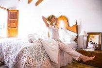 Jeune femme qui s'étend sur lit matin — Photo de stock