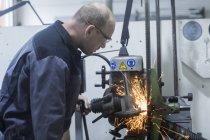 Homem adulto caucasiano que monitora a máquina de moedura na oficina — Fotografia de Stock
