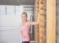 Woman stretching on wall bar in gym — Stock Photo