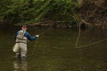 Людина, що риболовля на річці — стокове фото