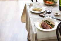 Table avec des assiettes de magret de canard, carottes, asperges et purées de pommes de terre et tarte aux pommes — Photo de stock