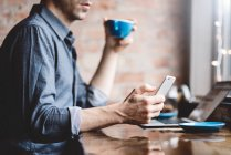Hombre usando el teléfono móvil en la cafetería - foto de stock