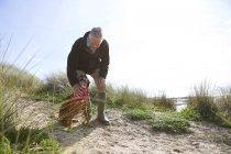 Chien de compagnie homme caressant sur les dunes de sable, baie de Constantine, Cornwall, Royaume-Uni — Photo de stock