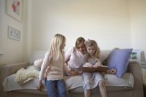 Mid adult woman and daughters reading storybook on sofa — Stock Photo