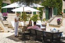 Бутік Готель офіціанткою, де подають шампанське щоб пара на патіо, Майорка, Іспанія — стокове фото