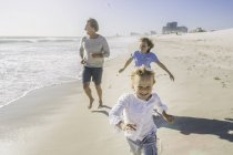Father and children running on beach — Stock Photo