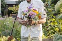 Uomo maggiore in giardino che tiene mazzo di fiori freschi recisi — Foto stock