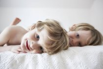 Boys lying on bed, smiling, looking at camera — Stock Photo