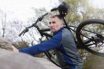 Homme mature VTT portant vélo sur la formation de roche — Photo de stock