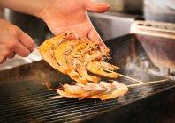 Chef cuisinier crevettes sur gril — Photo de stock