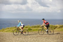 Cyclists riding on gravel road overlooking ocean — Stock Photo