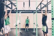 Two male cross trainers training on exercise bar in gym — Stock Photo