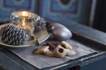 Vista cercana de las cookies, pino cono y vela titular en la rústica mesa de madera - foto de stock