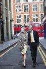 Couple habillé et dehors marchant dans la rue — Photo de stock