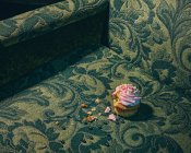 Cupcake and crumbs on armchair surface — Stock Photo