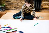 Boy sitting on floor drawing on large paper — Stock Photo