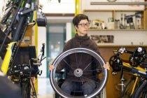 Жінка в інвалідному візку в магазині ремонт велосипедів, тримає кермо велосипеда — стокове фото