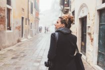 Young woman with camera looking over her shoulder on street, Venice, Italy — Stock Photo
