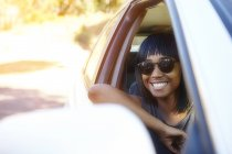 Portrait of young woman, looking out of car window — Stock Photo