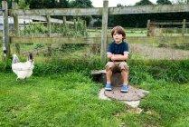 Niño sentado en la granja con pollo - foto de stock