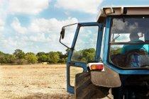 Bauer sitzt in Traktor auf Getreidefeld — Stockfoto