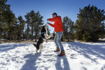 Mature man playing with dog in snow covered forest — Stock Photo