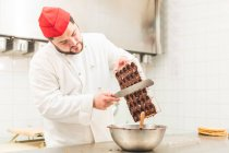 Chef scraping chocolate from chocolate mould — Stock Photo