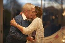 Романтическая старшая пара обнимается в подарочной коробке — стоковое фото