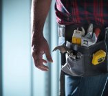 Man wearing tool belt with selection of tools and nails — Stock Photo