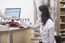 Young woman using wheelchair paying with credit card in shop — Stock Photo