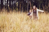 Two young girls running through meadow, hand in hand — Stockfoto