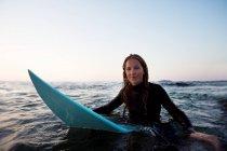 Donna che si siede sulla tavola da surf in acqua — Foto stock
