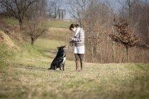 Взрослая женщина гуляет со своей собакой в поле — стоковое фото
