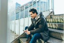 Людина, що сидить на крок за допомогою смартфона посміхається — стокове фото