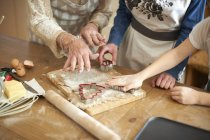 Cropped shot of senior woman and granddaughters cutting Christmas tree cookies at kitchen counter — Stock Photo