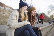 Zwei Freundinnen sitzen auf Stufen im Freien — Stockfoto
