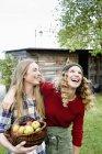 Deux femmes au jardin avec panier de pommes, rire — Photo de stock