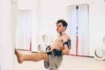Mann im Fitnessstudio trägt Pulsmesser und tritt Boxsack — Stockfoto