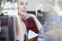 Junge Frau sitzt im Café und schaut aus dem Fenster — Stockfoto