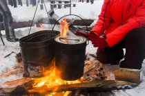 Cropped view of woman warming hands on campfire, Russia — Stock Photo