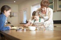 Donna anziana e nipoti pasta rotolamento per i biscotti dell'albero di Natale — Foto stock
